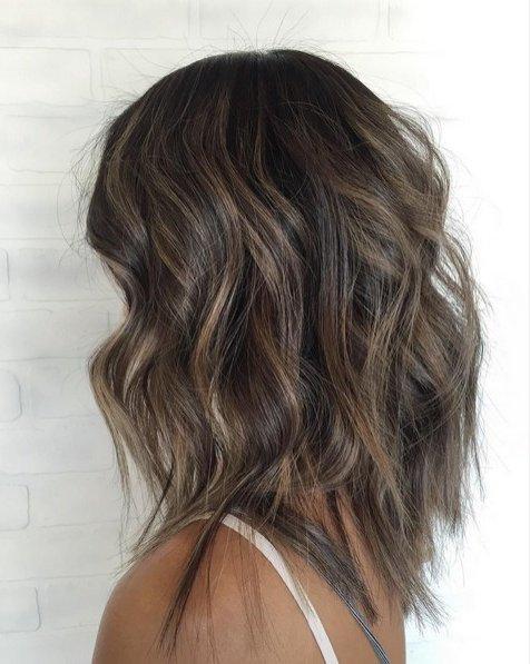 El cabello negro con luces y mechas que iluminan el rostro